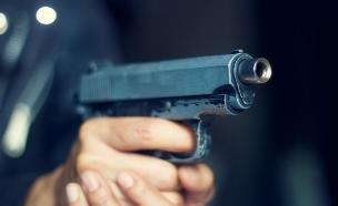 אדם מחזיק אקדח (צילום: thinkstock ,thinkstock)
