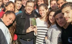 הרצוג מחלק עותקים של הספר לתלמידים (צילום: מתוך הפיסבוק של יצחק הרצוג)