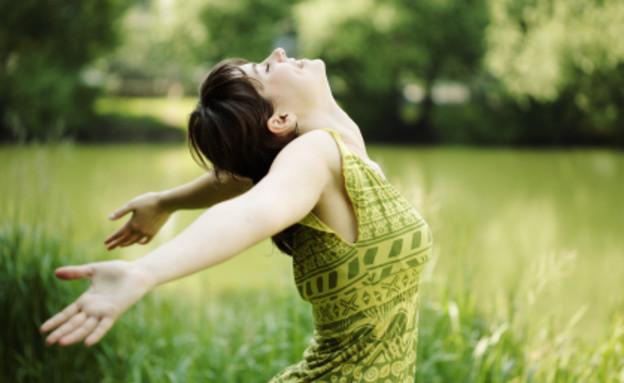 אישה לובשת שמלה ירוקה ברקע של דשא,מתמתחת לאחור (צילום: mako  ,istockphoto)