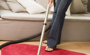 אישה בורוד שואבת אבק משטיח ורוד ומאחוריה ספה וחלון