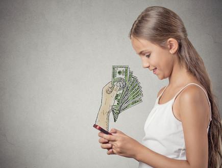 נערה גולשת בסמארטפון ומקבלת כסף (אילוסטרציה: shutterstock)