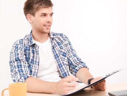 גבר יושב בחדר עם עט ונייר (אילוסטרציה: shutterstock)