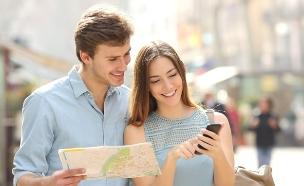 """זוג מטייל בחו""""ל עם מפה וסלולרי (צילום: Antonio Guillem, Shutterstock)"""