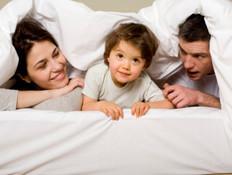 הורים וילד במיטה (צילום: אימג