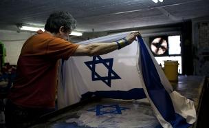 פועל בסדנה לייצור דגלים של קלמן ברמן רקמה ודגלים בירושלים (צילום: יונתן סינדל ,פלאש 90)