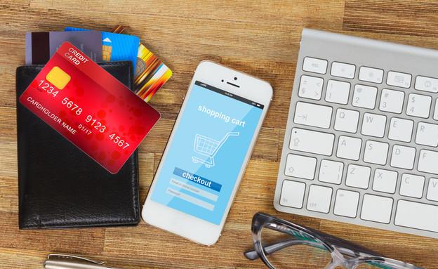 כרטיסי אשראי ליד סמארטפון עם אתר קניות (אילוסטרציה: shutterstock ,shutterstock)