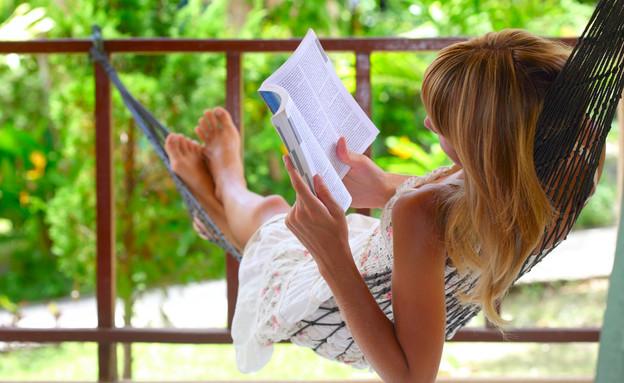 אישה קוראת ספר בחופשה (צילום: Dudarev Mikhail, Shutterstock)