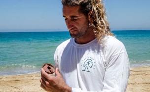 המציל בחוף מציג את הממצא ההיסטורי (צילום: יולי שוורץ, דוברת רשות העתיקות)