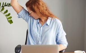 אישה מזיעה במשרד (אילוסטרציה: shutterstock ,mako)