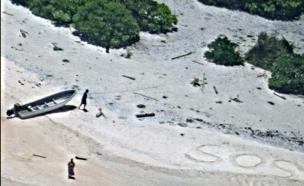 ה-SOS שציירו האמריקניים על החוף (צילום: הצי האמריקני)