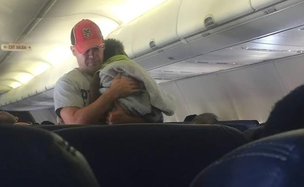 גבר מחזיק תינוק במטוס (צילום: פייסבוק)