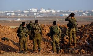 חיילים צופים על עזה (צילום: רויטרס)
