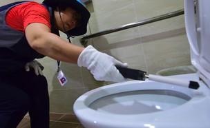 אישה סורקת תא שירותים בסיאול בחיפוש אחרי מצלמות נס (צילום: Getty Images ,Getty images)