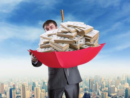 איש עסקים מחזיק ערימה של כסף במטרייה (אילוסטרציה: shutterstock ,shutterstock)
