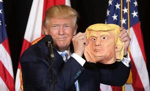 דונלד טראמפ מחזיק מסיכה של עצמו בעצרת בפלורידה (צילום: getty images ,getty images)