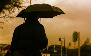 אישה תחת מטריה ביום חורפי גשום (צילום: חדשות 2)