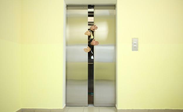 ידיים פותחות דלת של מעלית תקוע (אילוסטרציה: shutterstock ,shutterstock)