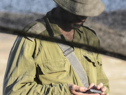 חייל בודק סמארטפון (צילום: ShutterStock ,ShutterStock)