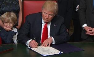 דונאלד טראמפ חותם על מסמך נשיאותי לאחר ההשבעה (צילום: חדשות 2)