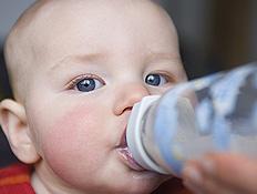 תינוק שותה מבקבוק ומביט למצלמה (צילום: jupiter images)
