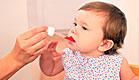 תינוקת יפה מקבלת תרופה אדומה מהיד של אמא שלה (צילום: jupiter images)