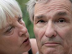 אישה מבוגרת מדברת לאוזנו של איש מבוגר