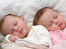 תינוקות תאומים ישנים עם הראש על הצד (צילום: istockphoto)