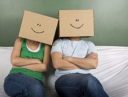 זוג יושב עם ארגזי קרטון וחיוך מצויר על הראש (צילום: kutay tanir, Istock)