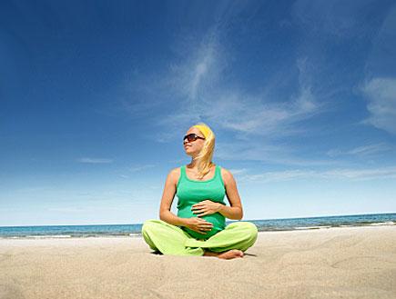 אישה בהריון יושבת על חוף הים (צילום: abu, Istock)