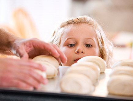 ילדה מסתכלת על כדורי בצק בתבנית (צילום: istockphoto)