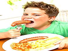 ילד אוכל נקניקיה וצלחת של צ'יפס לידו (צילום: jupiter images)