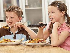 ילד וילדה אוכלים ארוחה וצופים בטלויזיה