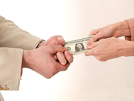 ידיים של אישה וגבר מושכות שטר של דולר (צילום: jupiter images)