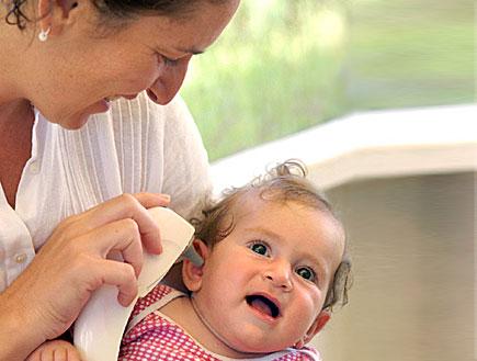 אמא מודדת חום לבתה עם מדחום באוזן (צילום: jupiter images)
