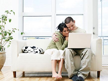 זוג מחובק ומחויך על ספה (צילום: lisegagne, Istock)