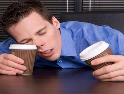 עייפות ותזונה-אדם נרדם על שולחן,מחזיק 2 כוסות קפה