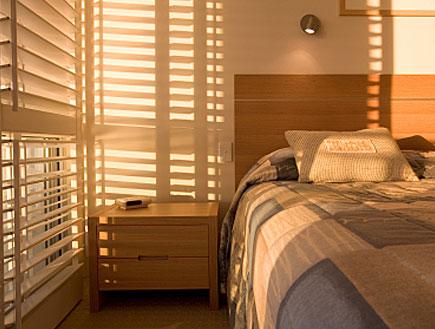חדר שינה יפה ועליו אור מחלון תריסים גדול (צילום: jupiter images)