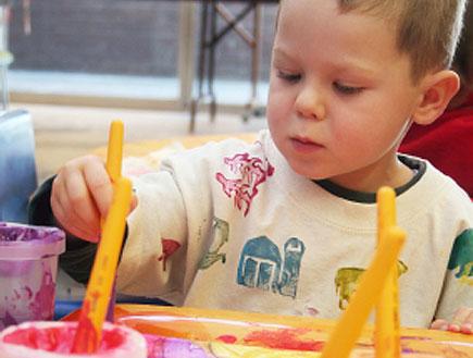 ילד יושב ומצייר ציור עם מכחולים וצבעים (צילום: Acik, Istock)
