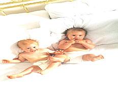 תינוקות תאומים שוכבים על מיטה ומרימים רגליים