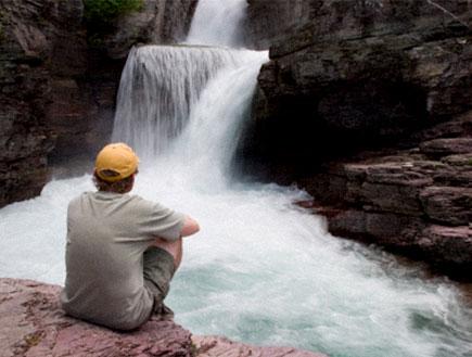 מדריך ויפסאנה-אדם בכובע צהוב יושב מול מפל מים (צילום: Forest Woodward, Istock)