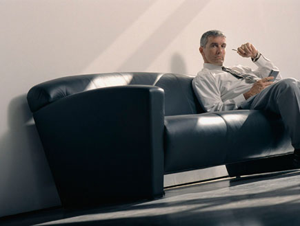 בוס יושב על ספה שחורה מחזיק עט ופנקס (צילום: jupiter images)