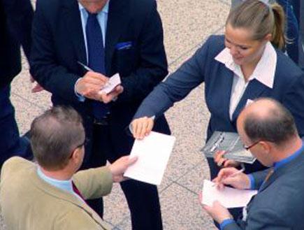 אישה בחליפה מחלקת דפים לאנשים בחליפות (צילום: Shutterstock)