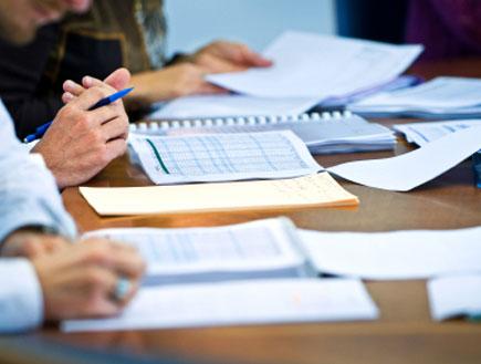 דפים מונחים על שולחן וחלקי אנשים בחליפות (צילום: Nikada, Istock)