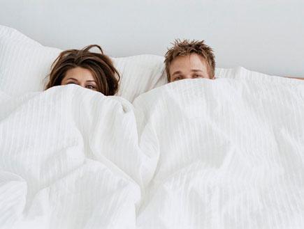זוג מציץ מבעד לשמיכה על מיטה לבנה (צילום: jupiter images)