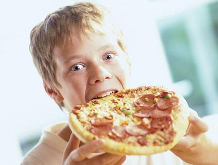 ילד בלונדיני אוכל פיצה עם נקניק (צילום: jupiter images)