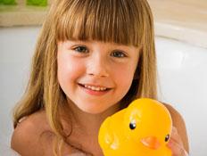 ילדה עם פוני באמבטית קצף מחזיקה ברווז צהוב ומחייכת (צילום: jupiter images)