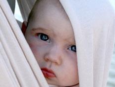תינוק יפה מציץ מתוך מנשא לבן וברקע ים (צילום: istockphoto)