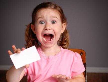 ילדה בורוד מחזיקה נייר לבן על שולחן עץ וצורחת מפחד (צילום: ideabug, Istock)