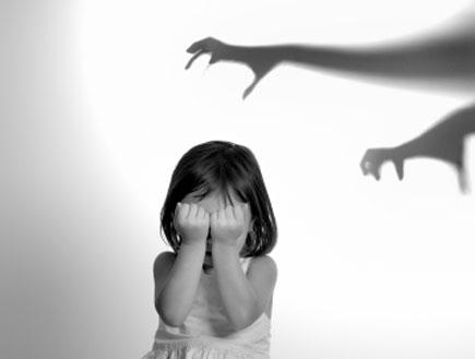 צל של ידיים מפחידות מעל ילדה מפוחדת בשחור לבן (צילום: istockphoto)