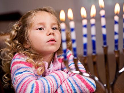 ילדה עם פסים מסתכלת על נרות דלוקים בחנוכיה (צילום: istockphoto)